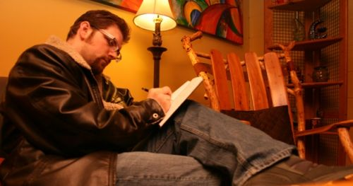 Cale Prindle writing in Crescent Moon Coffee Shop