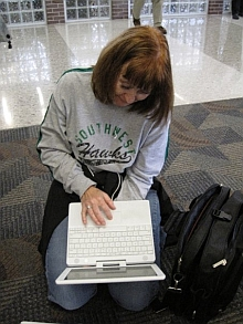 Cyndi Dwyer working on the floor on a laptop