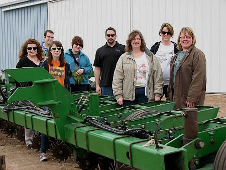 Writing Group standing by a cultivator