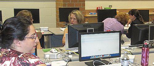 Teachers collaborating on computer work