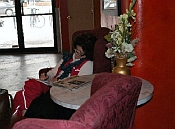 Woman writing in a burgundy chair