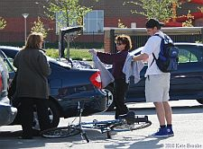 Diana Weis handing participants t-shirts from her car trunk
