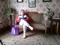 Sharon Bishop writing while sitting on a vintage sofa
